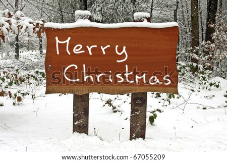Merry Christmas written on a snowy wooden sign in winter - stock photo