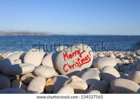 Merry Christmas written on heart shaped stone on the beach with spray brush - stock photo