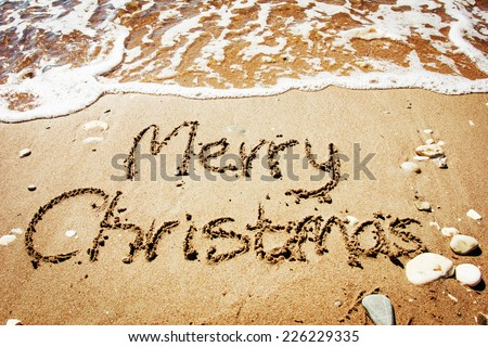Merry Christmas written on tropical beach sand  - stock photo