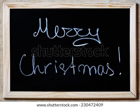 Merry Christmas written with white chalk on a blackboard - stock photo