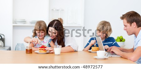 Merry family eating breakfast in the kitchen at home - stock photo