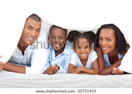 Merry family having fun lying down on bed at home - stock photo