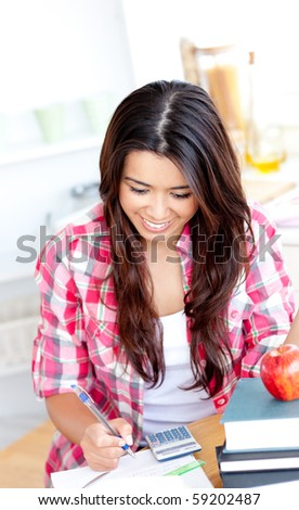 Merry female asian student doing math in the kitchen at home - stock photo