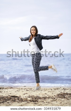 merry girl in a leather jacket and sneakers, jumping on the beach.