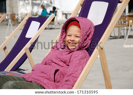 Merry girl is reclining in deck chair and basking in the sunshine. She is wearing warm clothes. She is looking at camera and smiling. She is resting at ski resort.