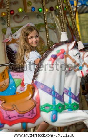 Merry-go-round  - little girl playing on carousel - stock photo