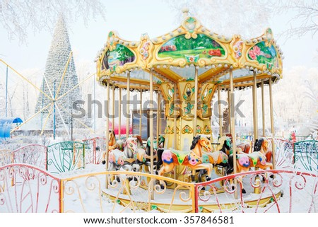 Merry-go-round with traditional horses covered with snow. Behind the carousel (roundabout) big Christmas tree. City park during the winter frosty day. - stock photo