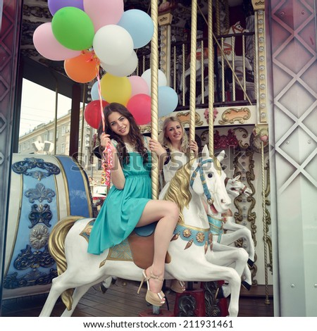 Merry-go-round young women playing on carousel, toned. - stock photo