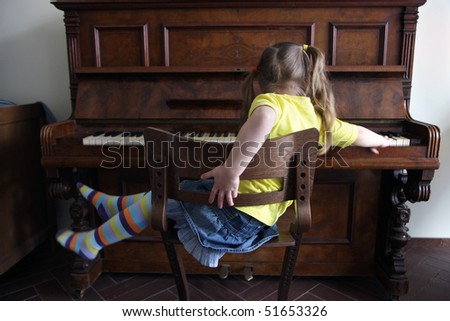 merry little girl, playing on piano - stock photo