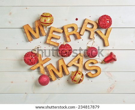 Merry Xmas composition of the wooden letters surrounded with the multiple decorations over the white colored wooden boards surface - stock photo