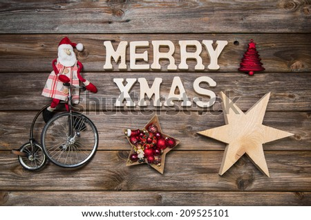 Merry Xmas greeting card with text. Red Santa Claus on wooden rustic background. - stock photo