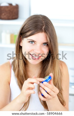 Merry young woman using cream for her lips in the bathroom