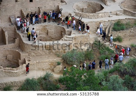 MESA VERDE, CO - JULY 26: A tour group gathers around a Native American ceremonial chamber as they prepare for a presentation by a Park Ranger July 26, 2008 in Mesa Verde, CO. - stock photo