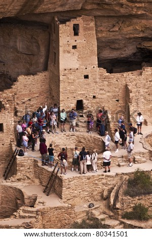 MESA VERDE NATIONAL PARK, CO - JUNE 19: A tour group visits the Cliff Palace ruin on June 19, 2011 at Mesa Verde National Park in Colorado.  Rangers lead guided tours of these famous ruins during the summer. - stock photo