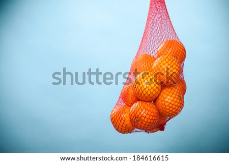 Mesh bag of fresh oranges healthy tropical fruits from supermarket on blue. Food retail. - stock photo