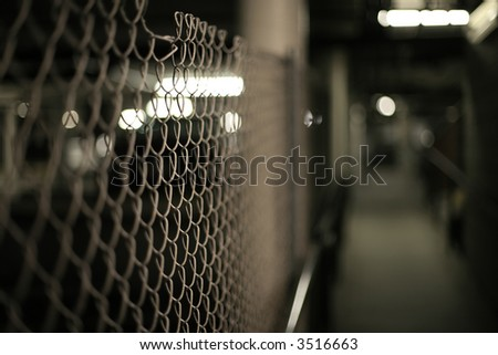 Mesh fence in an underground garage structure. Shallow DOF. - stock photo