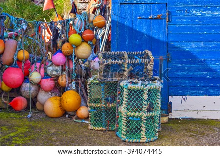 Mesh net shellfish traps and colorful buoys at the sea harbor of St. Abbs, Scotland. Crab or lobster pots on quayside. - stock photo