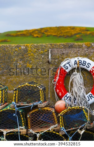 Mesh net shellfish traps at sea harbor of St. Abbs, Scotland. Crab or lobster pots on quayside. - stock photo