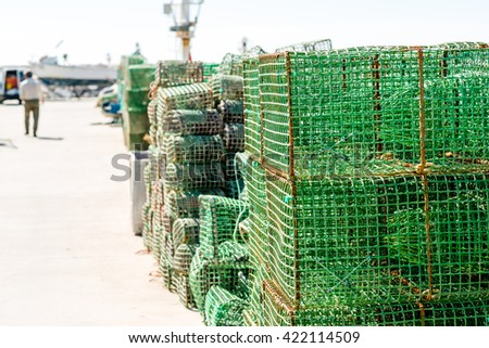 Mesh net shellfish traps at sea harbor with crab or lobster pots on quayside and a fishmonger in the background approaching his lorry - stock photo