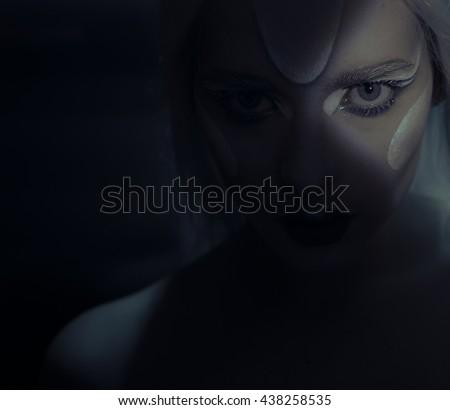 mesmerising eye of woman in dark scene portrait with frozen makeup  looking up - stock photo