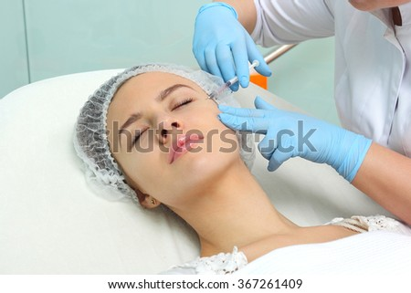 Mesotherapy. Beautiful woman gets an injection in her face. - stock photo