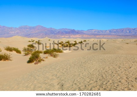 Mesquite Flat Sand Dunes are at the northern end of the valley floor and are nearly surrounded by mountains on all sides. - stock photo