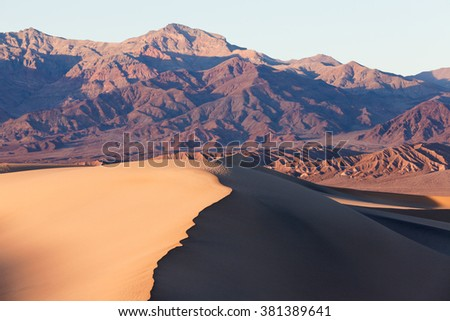 Mesquite Sand Dunes and colorful mountains in Death Valley National Park, California, USA - stock photo