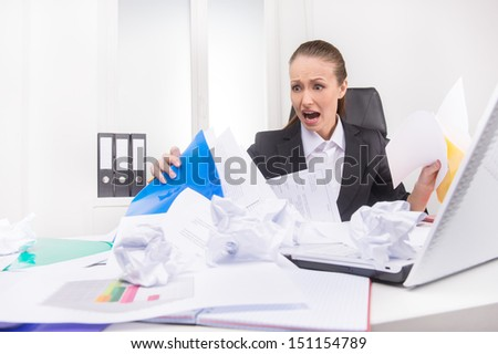 Mess on the working place. Shocked woman looking at the mess on her working place - stock photo