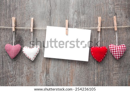 Message and red hearts on the clothesline against wooden background - stock photo
