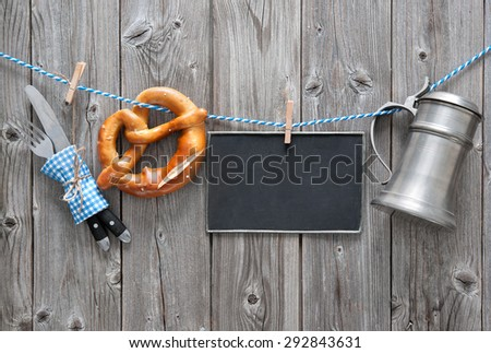 Message, beer mug and pretzel hanging on the clothesline against wooden board. Background for Oktoberfest - stock photo