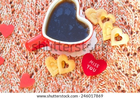 "Message close to a red cup of tea: ""Miss you"".  Shortcakes and a cup of tea in the form of a heart are on a knitted surface. Free space for a text. - stock photo"