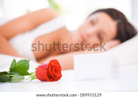 Message from boyfriend. Side view of beautiful young woman lying in bed with red rose  - stock photo