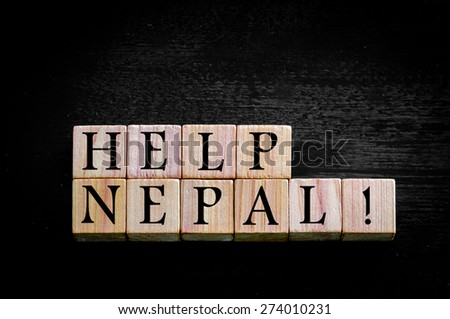 Message HELP NEPAL. Wooden small cubes with letters isolated on black background with copy space available. Concept image.