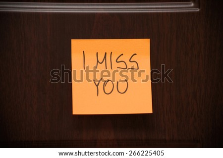 """Message """"I Miss You"""" handwritten on the sticky note on the wooden door - stock photo"""