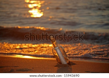 message in a bottle at sunset - stock photo