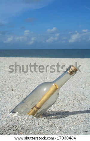 Message in a bottle buried in the sand - stock photo
