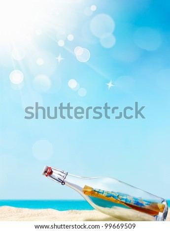 Message in a bottle illustrated with a beautiful sand beach in the background and a blue sky with awesome bokeh, maybe for your individual summer concept - stock photo