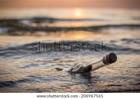 Message in a bottle in the sea sunset - stock photo