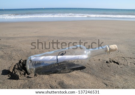 Message in a bottle on a lonely beach ,in Tenerife, Spain - stock photo