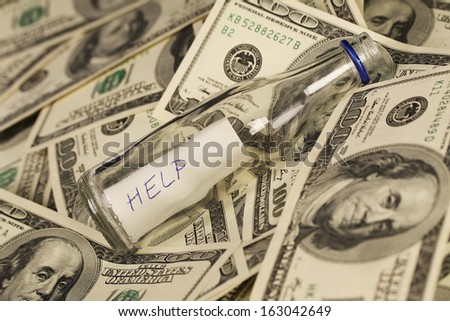 Message in a bottle on background with money american hundred dollar bills - horizontal