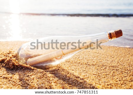 Message in a bottle on sand beach at sunset. Support and development
