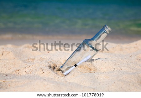 Message in a bottle on the sandy beach - stock photo