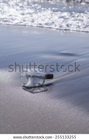 Message in a bottle sits in the sand on a tropical island beach / Message in a bottle  - stock photo