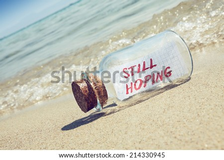 """Message in a bottle """"Still hoping"""" on sandy beach. Creative hope and faith concept.  - stock photo"""