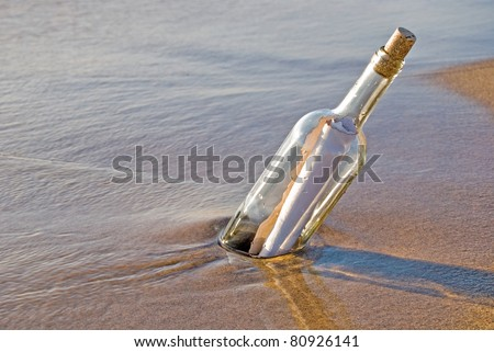message in a bottle stuck in sand - stock photo