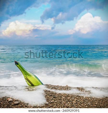 Message in the old bottle on the beach - stock photo