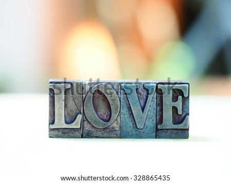 Message love spelled in iron letterpress block  with copy space and blurred bokeh background, love word, L O V E