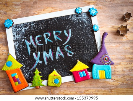 "Message ""Merry Christmas"" on blackboard decorated with colorful  homemade christmas cookies and sugar. - stock photo"