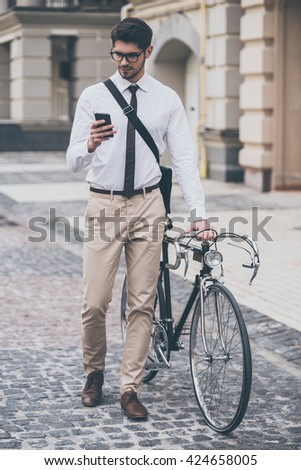 Message on a go. Confident young man in glasses using his smartphone and holding hand on his bicycle while standing outdoors - stock photo
