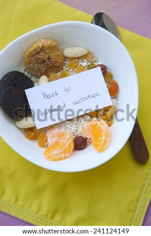 """Message on the plate with healthy breakfast: """"Back to balanced nutrition."""" Food background: dried figs,tangerine,raisins,oat flakes,almonds,nuts,hazelnuts. - stock photo"""